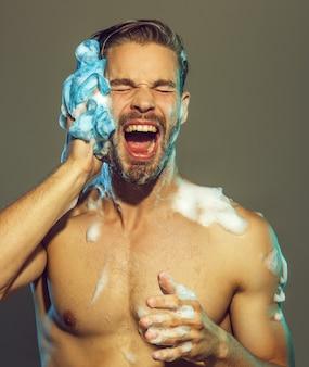 Gespierde aantrekkelijke bebaarde man die douche neemt portret van knappe sexy man met naakt bovenlichaam
