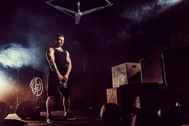 Gespierde aantrekkelijke kaukasische bebaarde man tillen twee kettlebells in een sportschool. halterschijven, halter en banden op achtergrond.