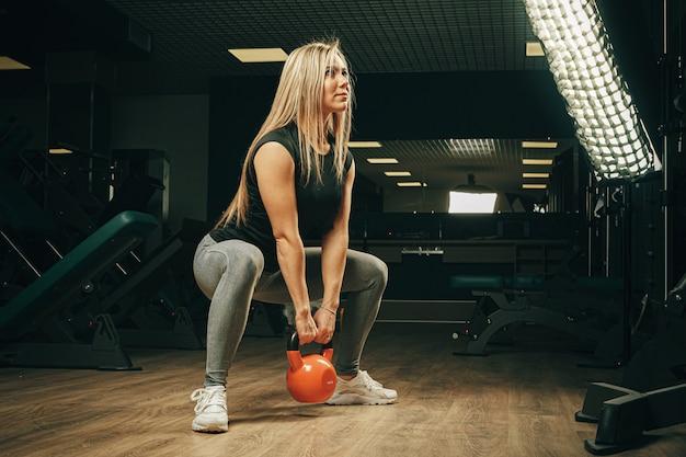 Gespierde aantrekkelijke vrouw in sportschool opheffing halters