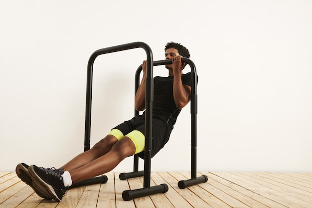Gespierde afro-amerikaanse atleet in zwarte trainingstoestel lichaamsgewicht rijen op mobiele bars tegen witte muur en lichte houten vloer.