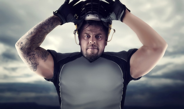Gespierde amerikaanse voetballer tegen donkere hemel
