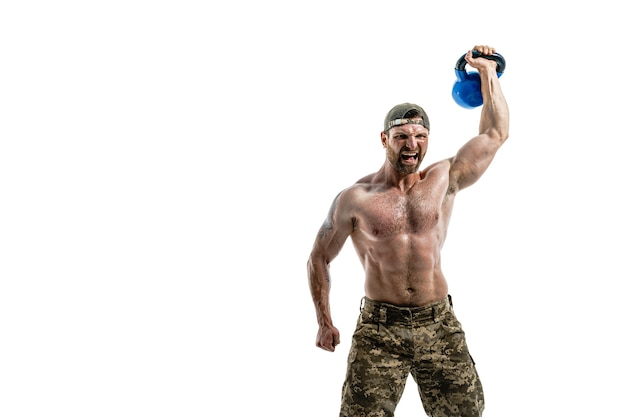 Gespierde atleet bodybuilder man in camouflage broek met een naakte torso training met kettlebell op een witte muur. isoleren