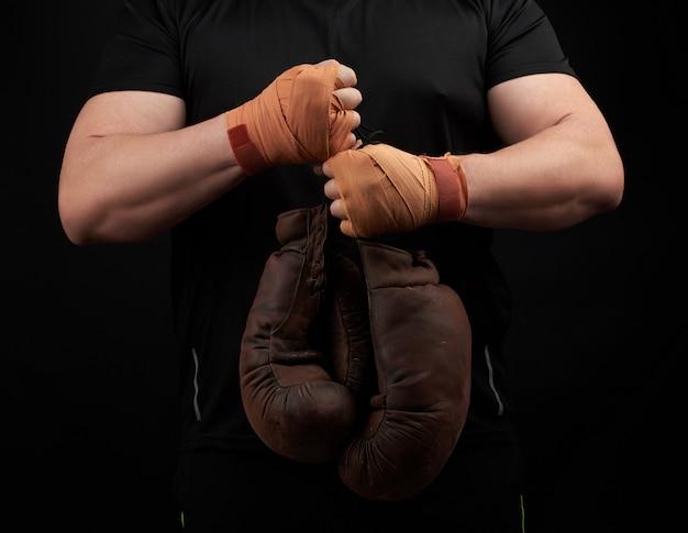 Gespierde atleet in een zwart uniform heeft zeer oude bruine bokshandschoenen in zijn hand