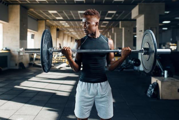 Gespierde atleet in sportkleding die oefening met barbell doet op training in de sportschool. training in sportclub, gezonde levensstijl