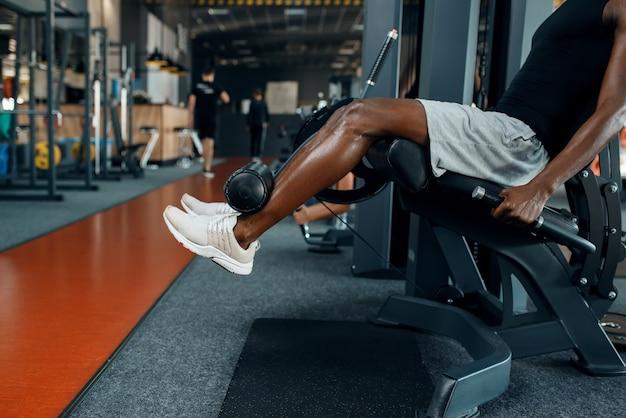 Gespierde atleet in sportkleding op hometrainer
