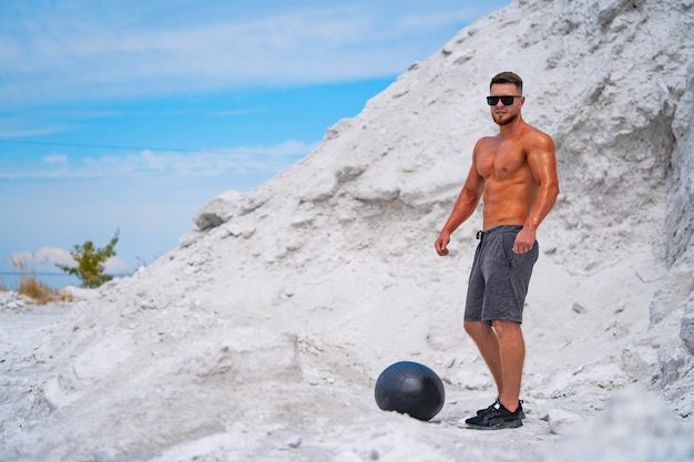 Gespierde atleet sterke man in zonnebril staat in de buurt van zwarte fitball