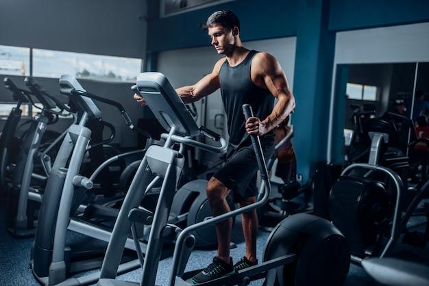 Gespierde atleet training benen op hometrainer. actieve sportoefeningen in de sportschool