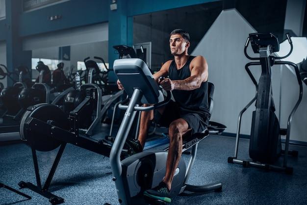 Gespierde atleet training benen op hometrainer