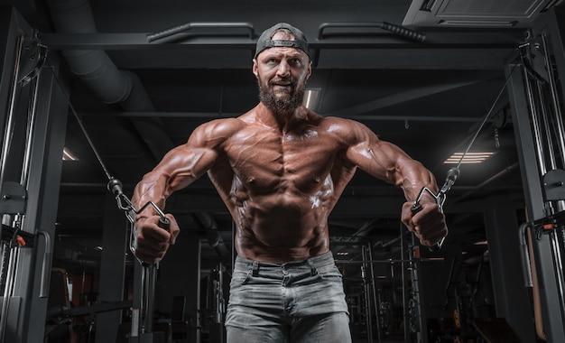 Gespierde atleet training in een cross-over in de sportschool. oppompen van de romp. fitness en bodybuilding concept.