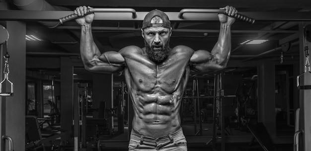 Gespierde atleet trekt in de sportschool. fitness en bodybuilding concept.