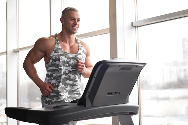Gespierde atletische bodybuilder fitness model met loopband sportschool in de buurt van groot raam