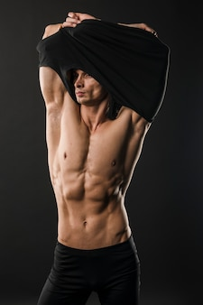 Gespierde atletische man t-shirt opstijgen