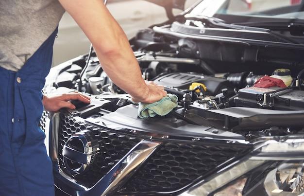 Gespierde auto service werknemer reparatie voertuig.