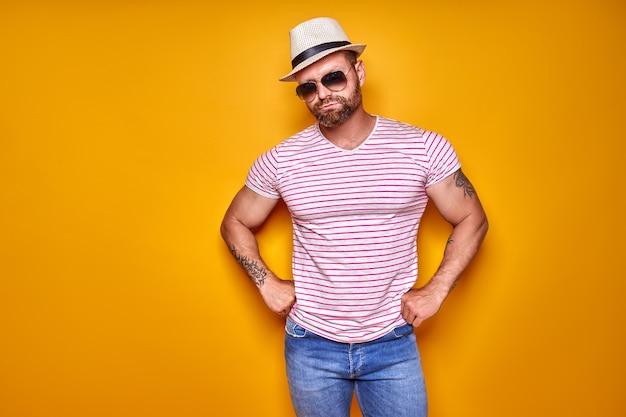 Gespierde bebaarde man in hemdjeans en stijlvolle hoedzonnebril die in studio over gele achtergr...