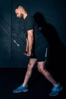 Gespierde bebaarde man trainen in de sportschool doen oefeningen op triceps.