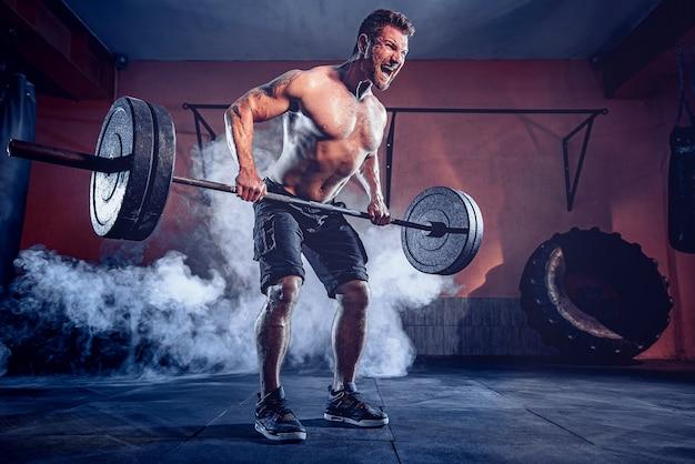 Gespierde bebaarde man trainen in de sportschool doen oefeningen, sterke mannelijke naakte torso abs. rook op de muur