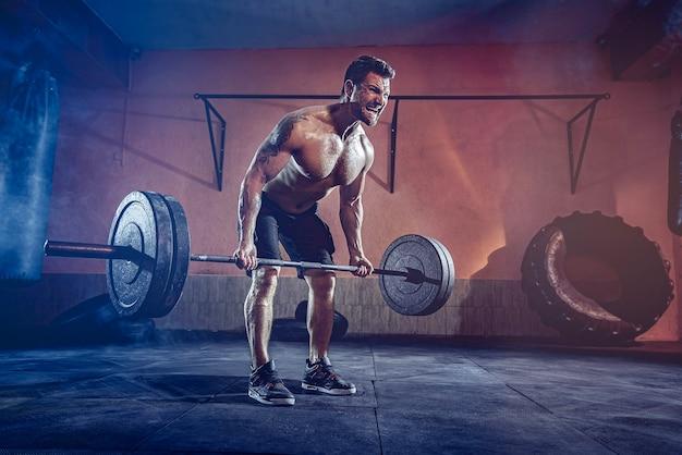 Gespierde bebaarde man trainen in de sportschool doen oefeningen, sterke mannelijke naakte torso abs.