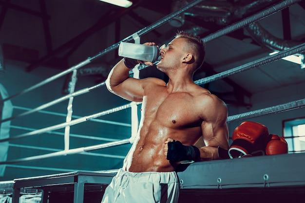 Gespierde blanke man op dieet rusten na boksoefening en drinkwater uit de shaker in de sportschool.