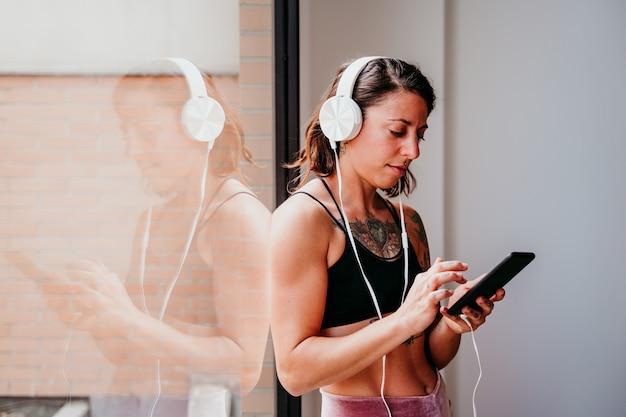 Gespierde blanke vrouw die naar muziek luistert op mobiele telefoon en headset in de sportschool. overdag bij het raam staan. sporten en een gezonde levensstijl