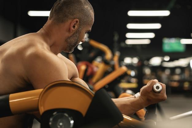 Gespierde bodybuilder die biceps-krullen doet tijdens zijn training in de sportschool