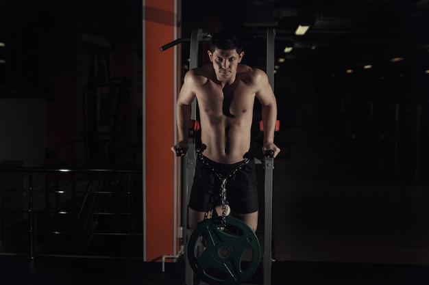 Gespierde bodybuilder die in de sportschool traint en oefeningen doet op parallelle staven. athlitische mannelijke naakte torso.