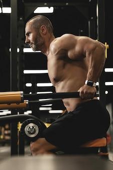 Gespierde bodybuilder doet dips voor triceps en borstspieren tijdens zijn training in de sportschool