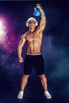 Gespierde bodybuilder doet oefening met kettlebell. geschoten met rook.