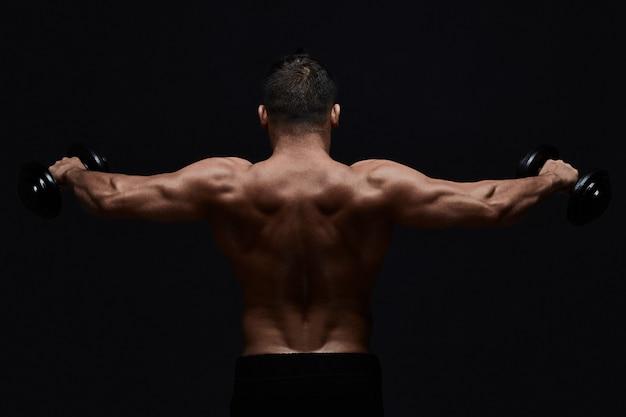 Gespierde bodybuilder doet oefeningen met halter over zwart. sterke atletische man toont lichaam, buikspieren, biceps en triceps.