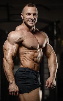 Gespierde bodybuilder fitness man doet abs oefeningen in de sportschool