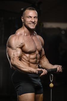 Gespierde bodybuilder fitness man doet armen oefeningen in de sportschool