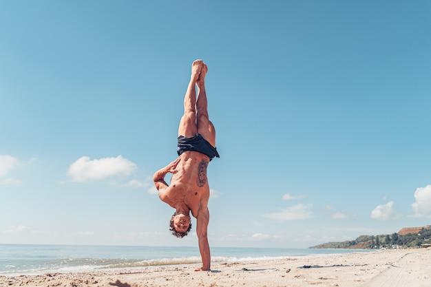 Gespierde bodybuilder fitness man met een naakte torso staat op één arm op het strand