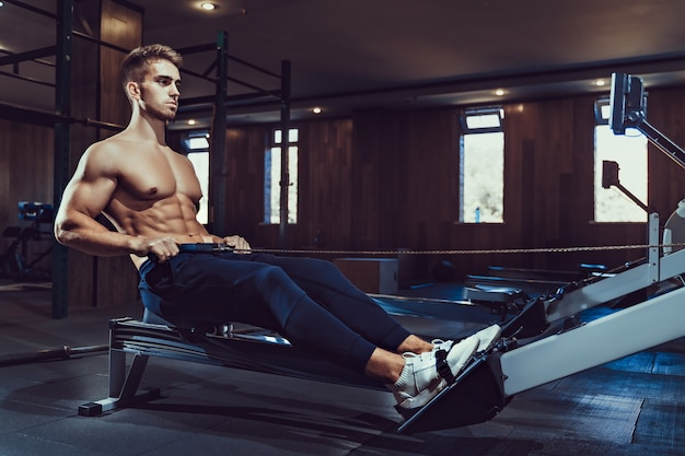 Gespierde bodybuilder in sportkleding opleiding terug zittend op hometrainer. zijaanzicht van man met perfecte body building lichaam in sportschool in donkere sfeer. concept van bodybuilding, fitness.