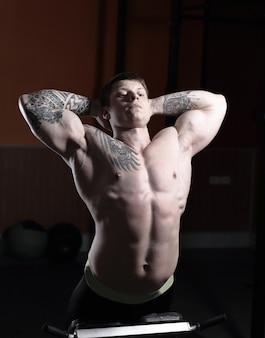 Gespierde bodybuilder knappe mannen doen oefeningen in de sportschool naakte torso fitness en bodybuilding. foto met kopie ruimte.