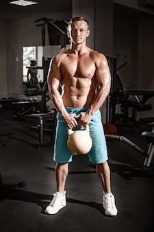 Gespierde bodybuilder man doen oefeningen met gewicht in de sportschool