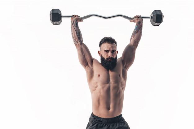 Gespierde bodybuilder man doen oefeningen met gewichten