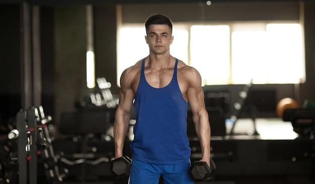 Gespierde bodybuilder man doet oefeningen met halters in sportschool