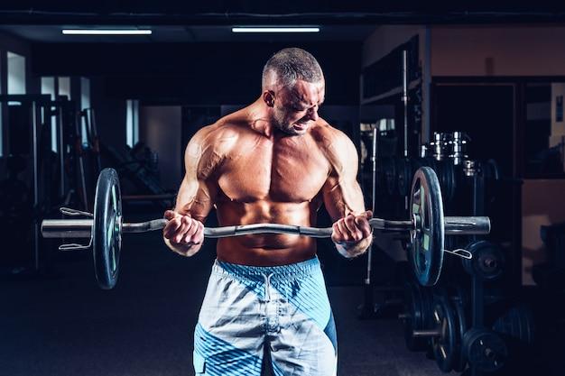 Gespierde bodybuilder man doet oefeningen op biceps met grote halter in sportschool