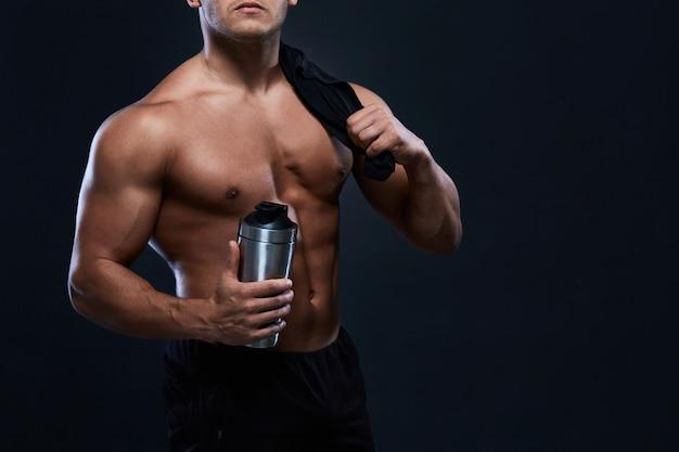 Gespierde bodybuilder met shaker-fles op zwart. sterke atletische man toont lichaam, buikspieren, borstspieren, biceps en triceps. trainen, aankomen in gewicht. bodybuilding.
