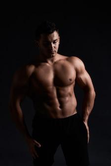 Gespierde bodybuilder op zwart. sterke atletische man toont lichaam, buikspieren, borstspieren, biceps en triceps. trainen, aankomen in gewicht. bodybuilding.