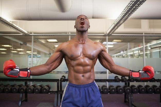 Gespierde bokser die in gezondheidsclub schreeuwen