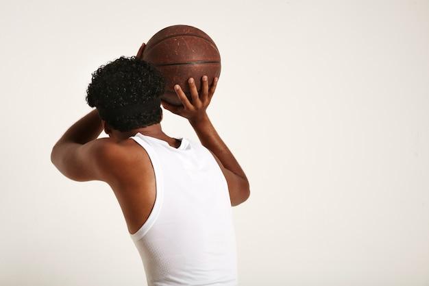 Gespierde donkere atleet met een afro en een hoofdband die een wit mouwloos shirt draagt en een oud bruin lederen basketbal op wit gooit