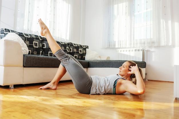 Gespierde fit sportvrouw crunches op de vloer thuis doen tijdens lockdown.