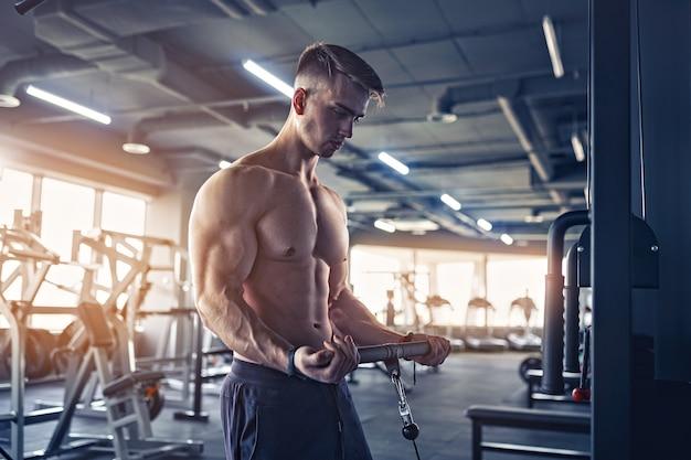 Gespierde fitness bodybuilder zwaar gewicht oefening voor biceps op machine met kabel in de sportschool