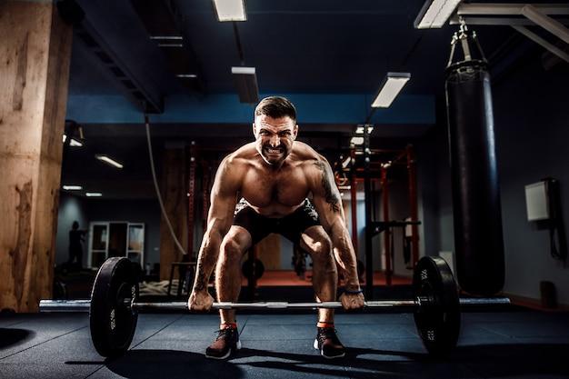 Gespierde fitness man doen deadlift een barbell in modern fitnesscentrum