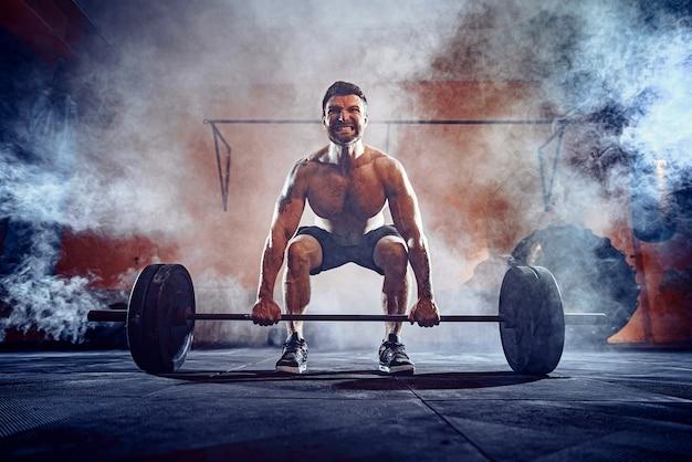 Gespierde fitness man doet deadlift een barbell boven zijn hoofd in het moderne fitnesscentrum. functionele training. snatch oefening. rook op de muur.
