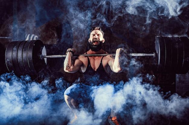 Gespierde fitness man doet deadlift een barbell boven zijn hoofd in moderne fitnesscentrum. functionele training.