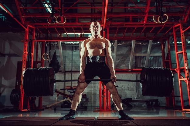 Gespierde fitness man doet deadlift een barbell in moderne fitnesscentrum. functionele training.