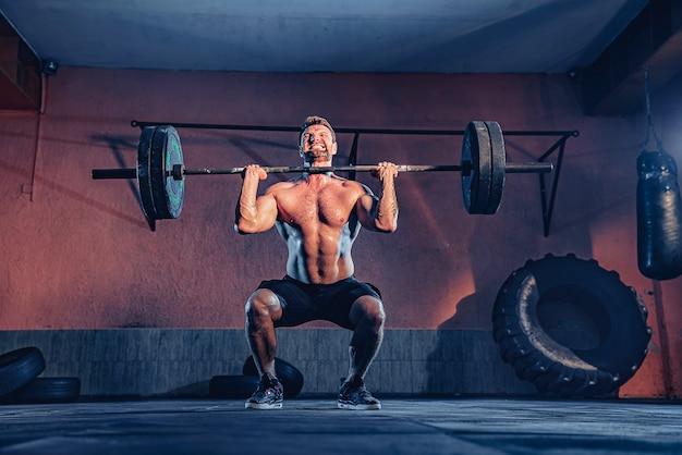 Gespierde fitness man doet een halter boven zijn hoofd in het moderne fitnesscentrum. functionele training. snatch oefening.