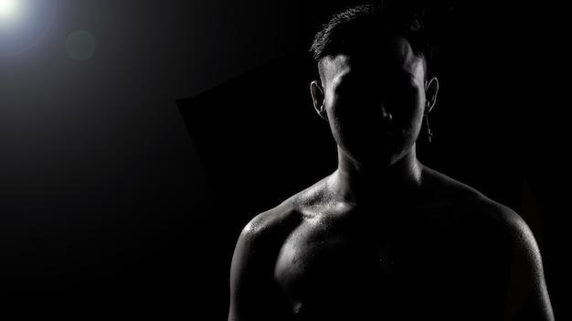 Gespierde fitness man oefent een gezonde levensstijl in donkere achtergrond silhouet
