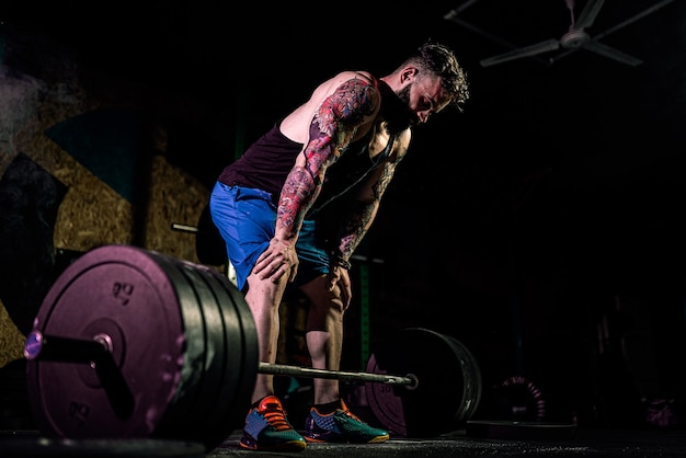 Gespierde fitness man voorbereiden om een barbell deadlift in moderne fitnesscentrum.